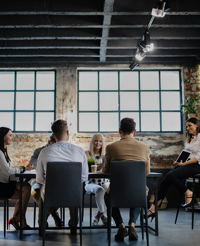 people at a meeting sitting around a table in an industrial building - tungsten network world class